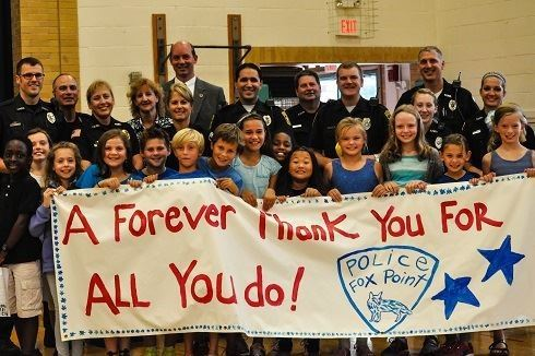 DARE Police Officers, Adults, and Children Holding Up a Thank You banner